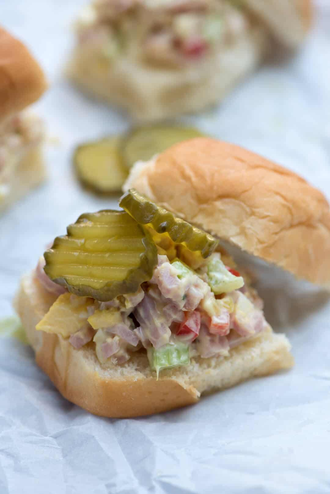 A closeup of Ham Salad on a slider bun with pickles.