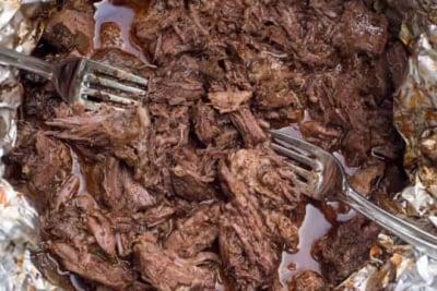 Two forks shredding beef in foil.