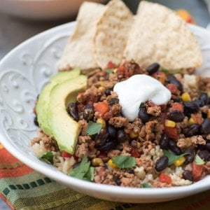 A bowl filled with turkey taco filling topped with sour cream and avocado.