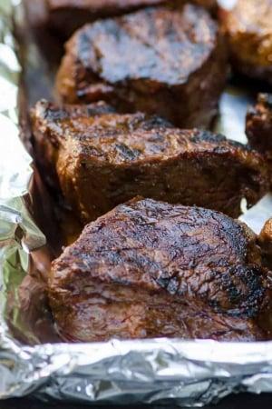 Grilled steak on a foil lined baking sheet.