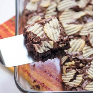 A spatula lifts a brownie topped with potato chips from a baking dish.