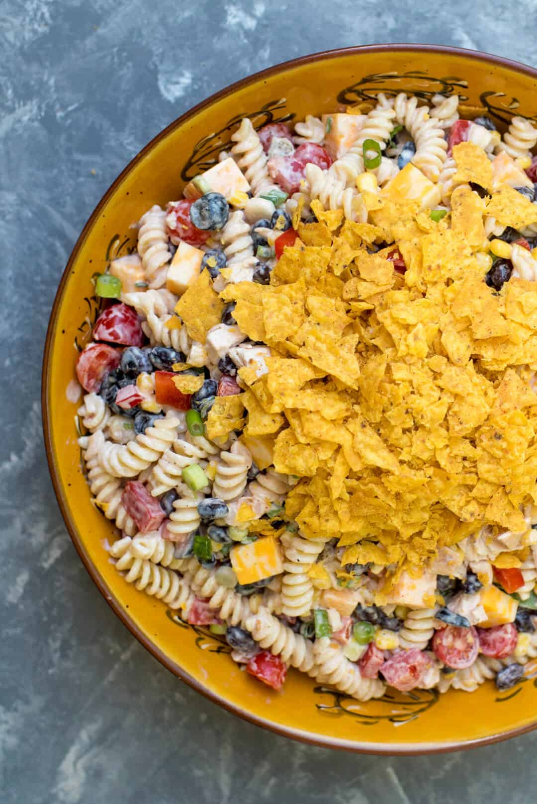 This Southwest Ranch Chicken Pasta Salad is loaded with vibrant, flavorful ingredients, tossed with a creamy salsa Ranch dressing and topped off with crushed Doritos®. A fun choice to make and take to any summer gathering.