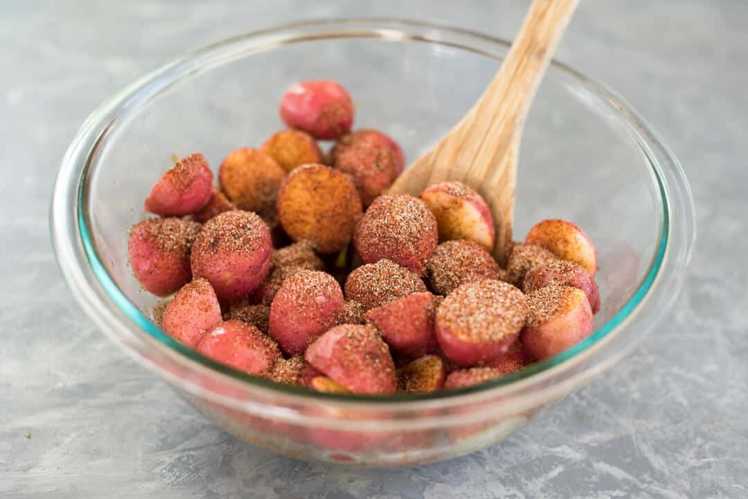 Halved mini red potatoes in a glass mixing bowl with coated olive oil and the BBQ spice mixture.