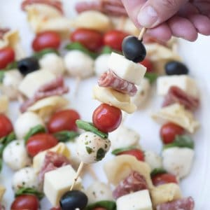 A close up of a hand lifting a skewer filled with cheese, meat, cherry tomato, and olive.