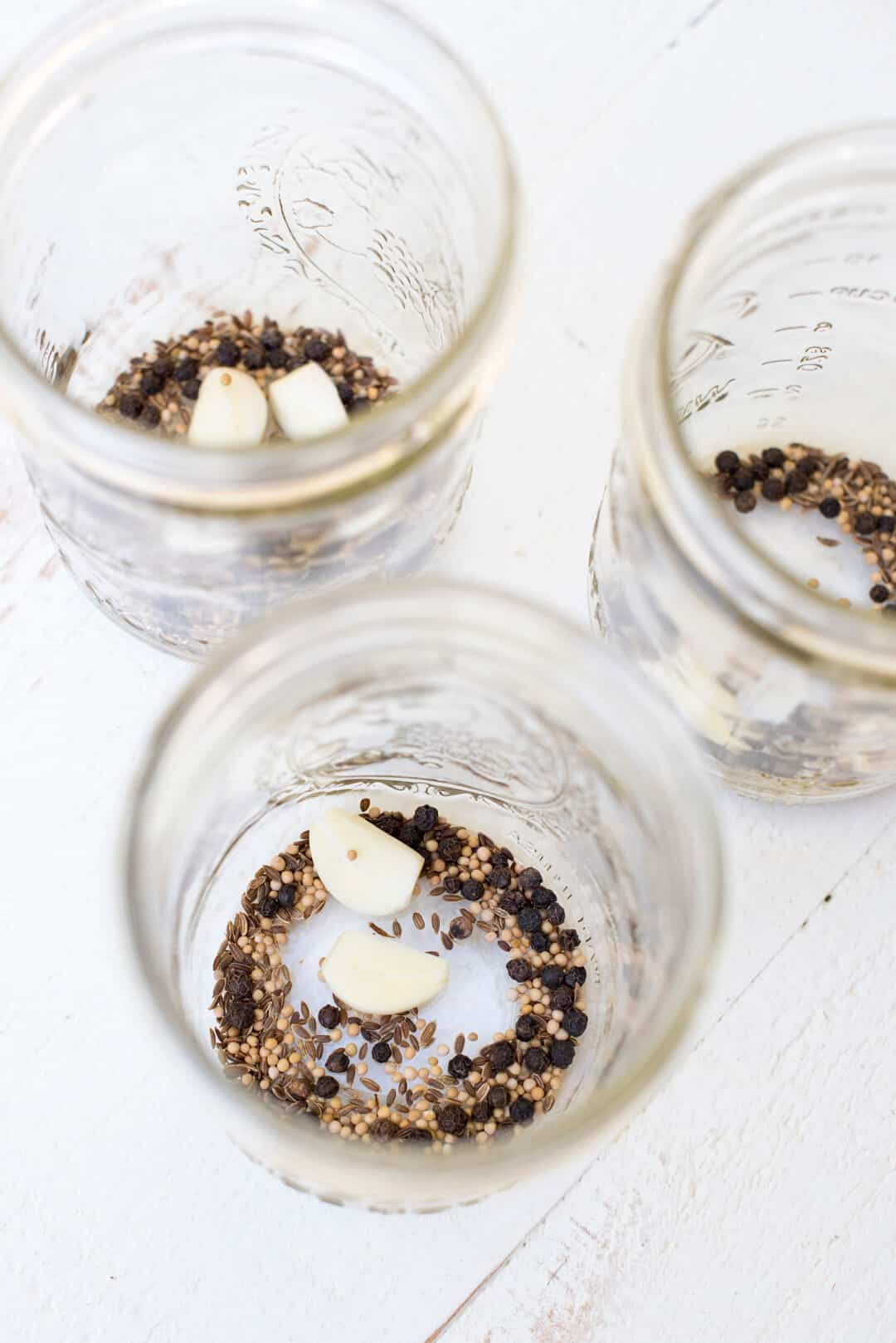 The pickling spices and garlic cloves in the bottom of three empty mason jars.