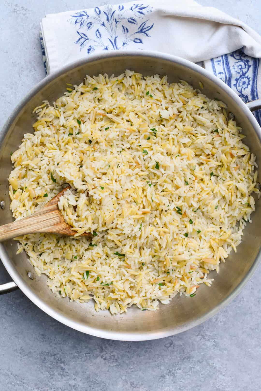 The pilaf in a stainless steel skillet with a wooden spoon.