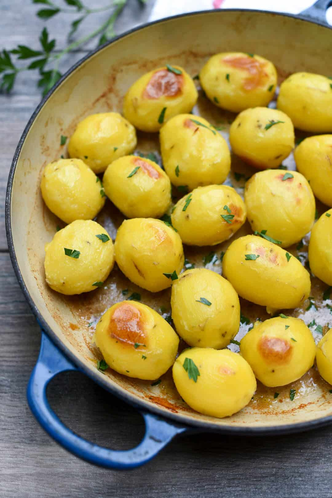 A blue skillet filled with Garlic and Butter Broth Roasted Potatoes.