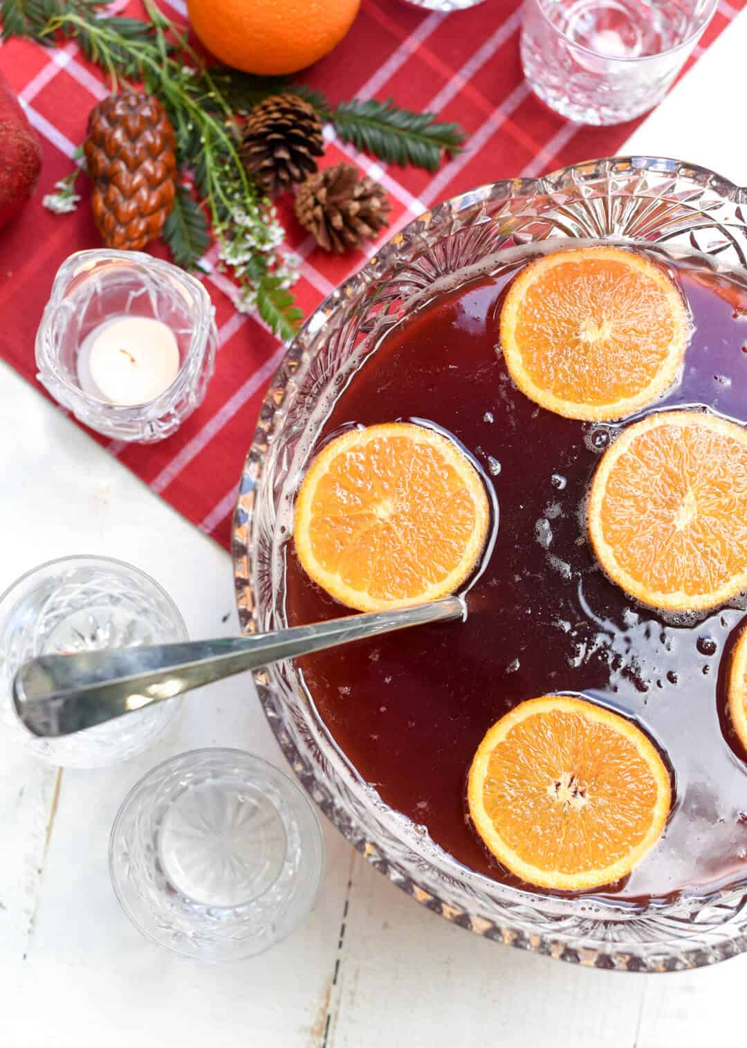 Orange slices float on the surface of the red punch in a punch bowl.