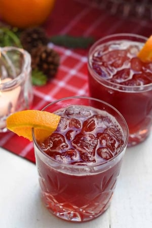 A close up of a red beverage with a slice of orange.
