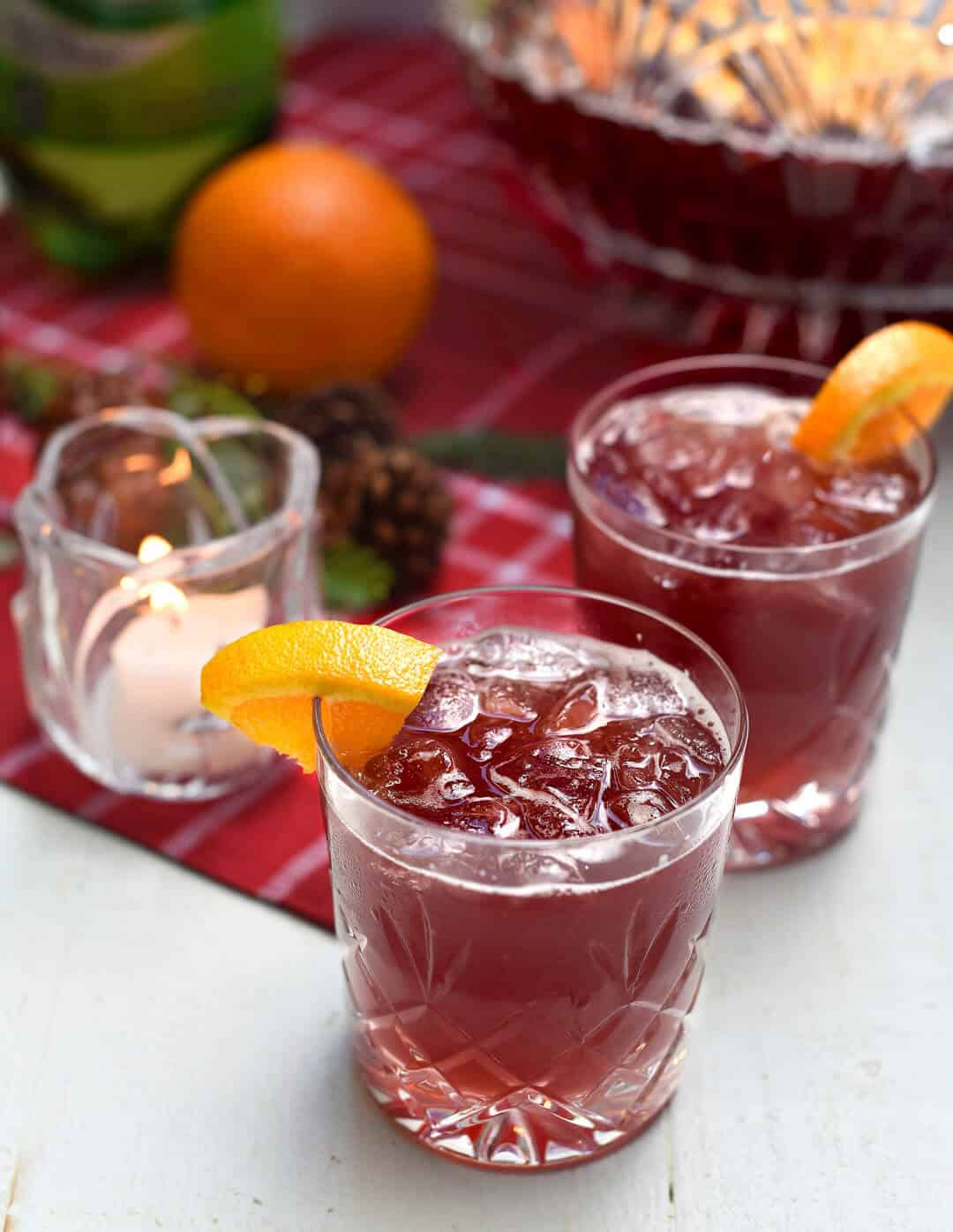 Two glasses of Sparkling Pomegranate Vodka Punch garnished with orange slices near a red cloth.