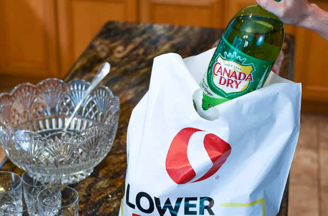 Canada Dry being lifted from a Safeway shopping bag.