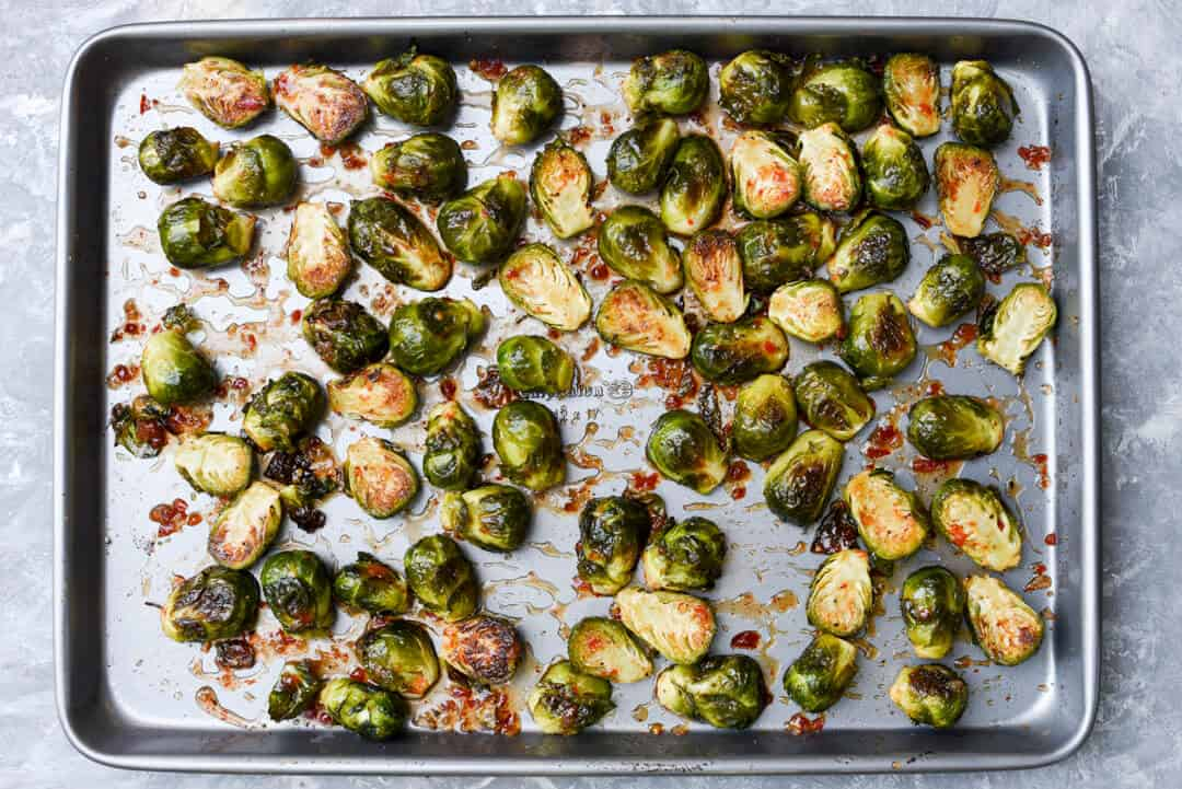 The Brussels sprouts are mixed with chili garlic sauce on the baking sheet.