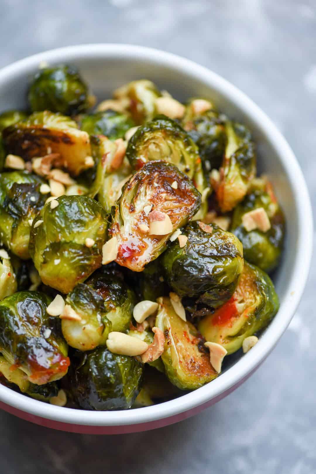 A close up of the Sweet Chili Garlic Brussels Sprouts topped with peanuts.