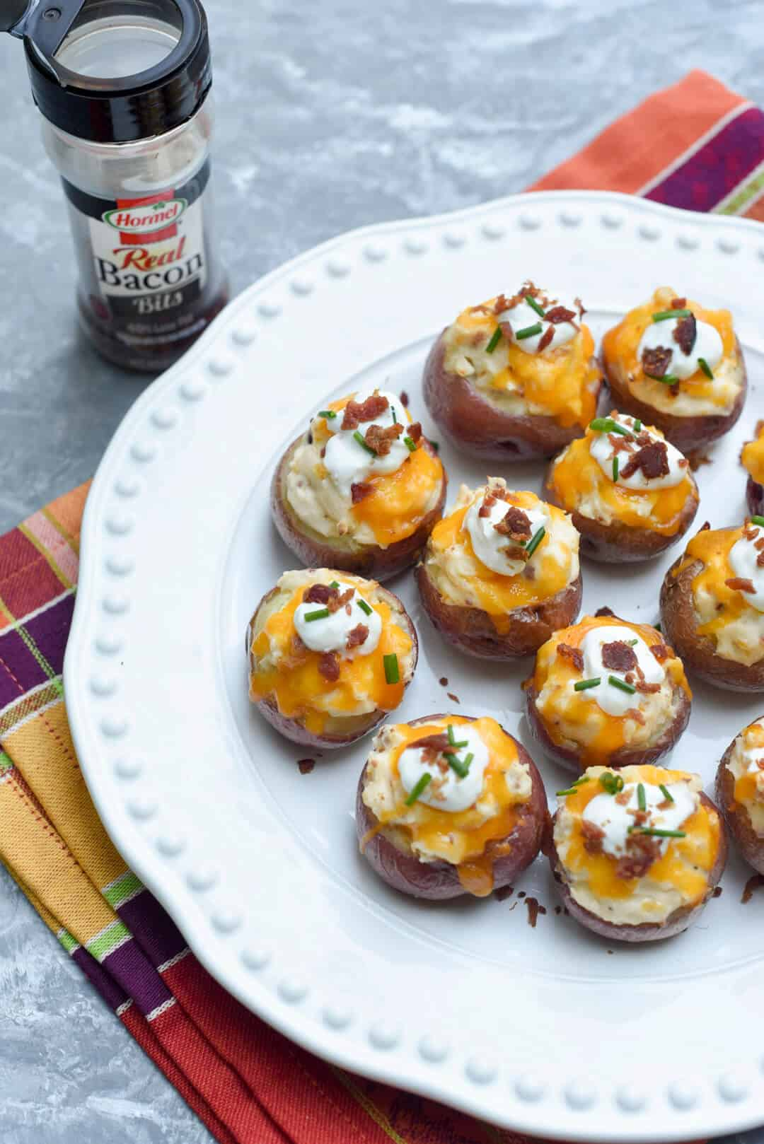 These Fully Loaded Twice Baked Potato Bites are stuffed with a creamy, cheesy, bacon-studded filling and garnished with sour cream, chives and more bacon!