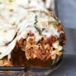 A spatula lifts a lasagna rollup from a baking dish.