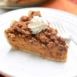 A slice of pumpkin pie with a praline topping and whipped cream on a white plate.