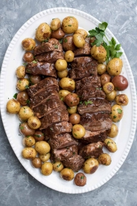 A platter with slices of pork tenderloin and potatoes.
