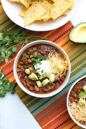A bowl of chili with toppings on a colorful cloth.