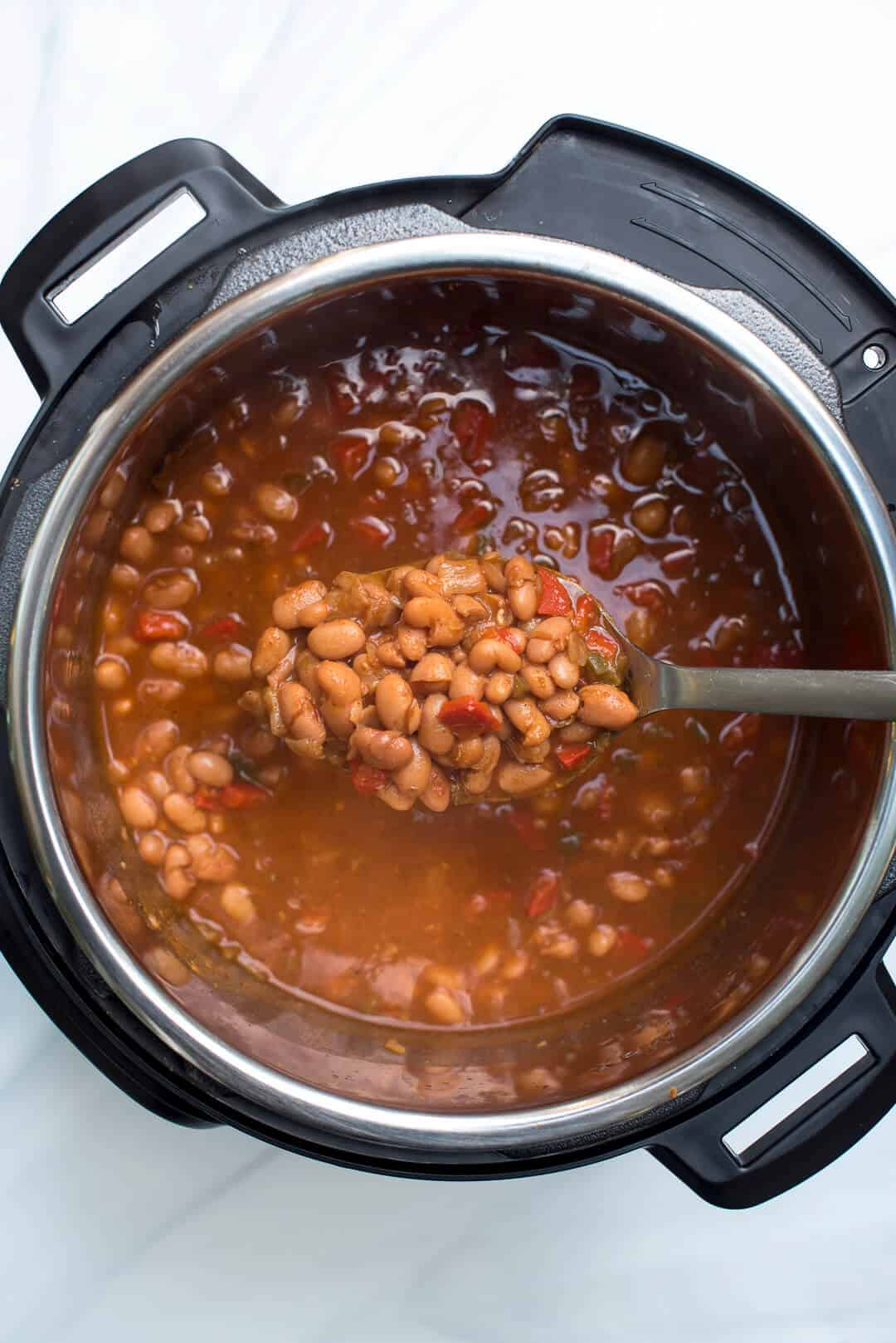 An over the top image showing a spoon lifting some of the Mexican Pinto Beans from the Instant Pot.