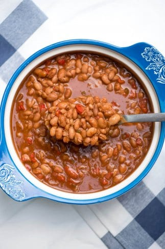 A spoon scoops up saucy beans from a blue and white bowl.