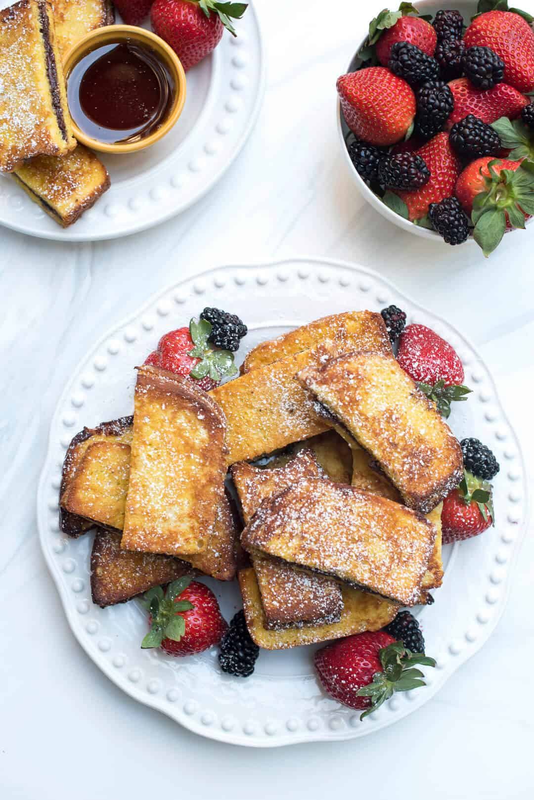 Stacks of Nutella French Toast Sticks with a side of berries.