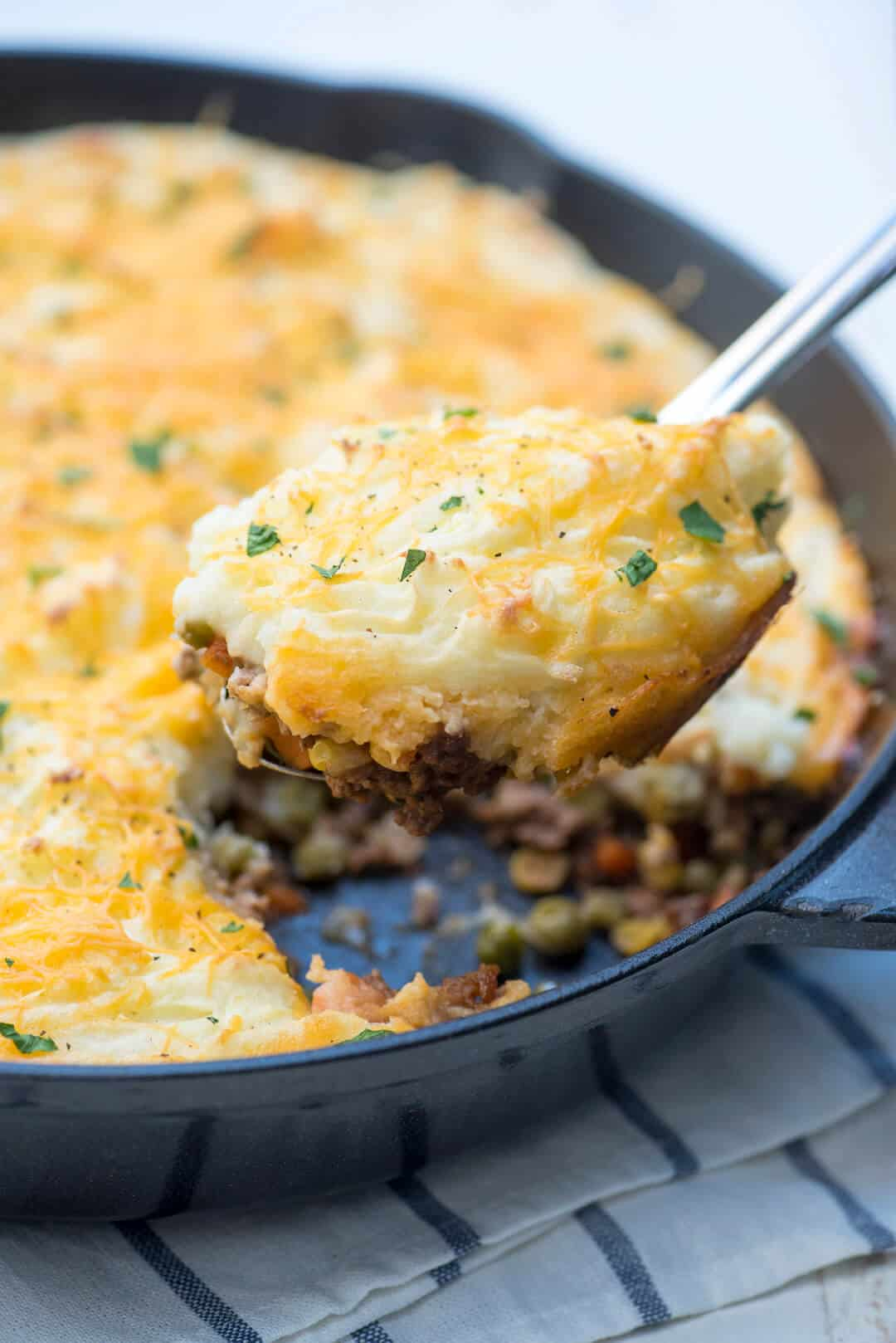 A serving spoon lifts a spoonful of the shepherd's pie from the skillet.