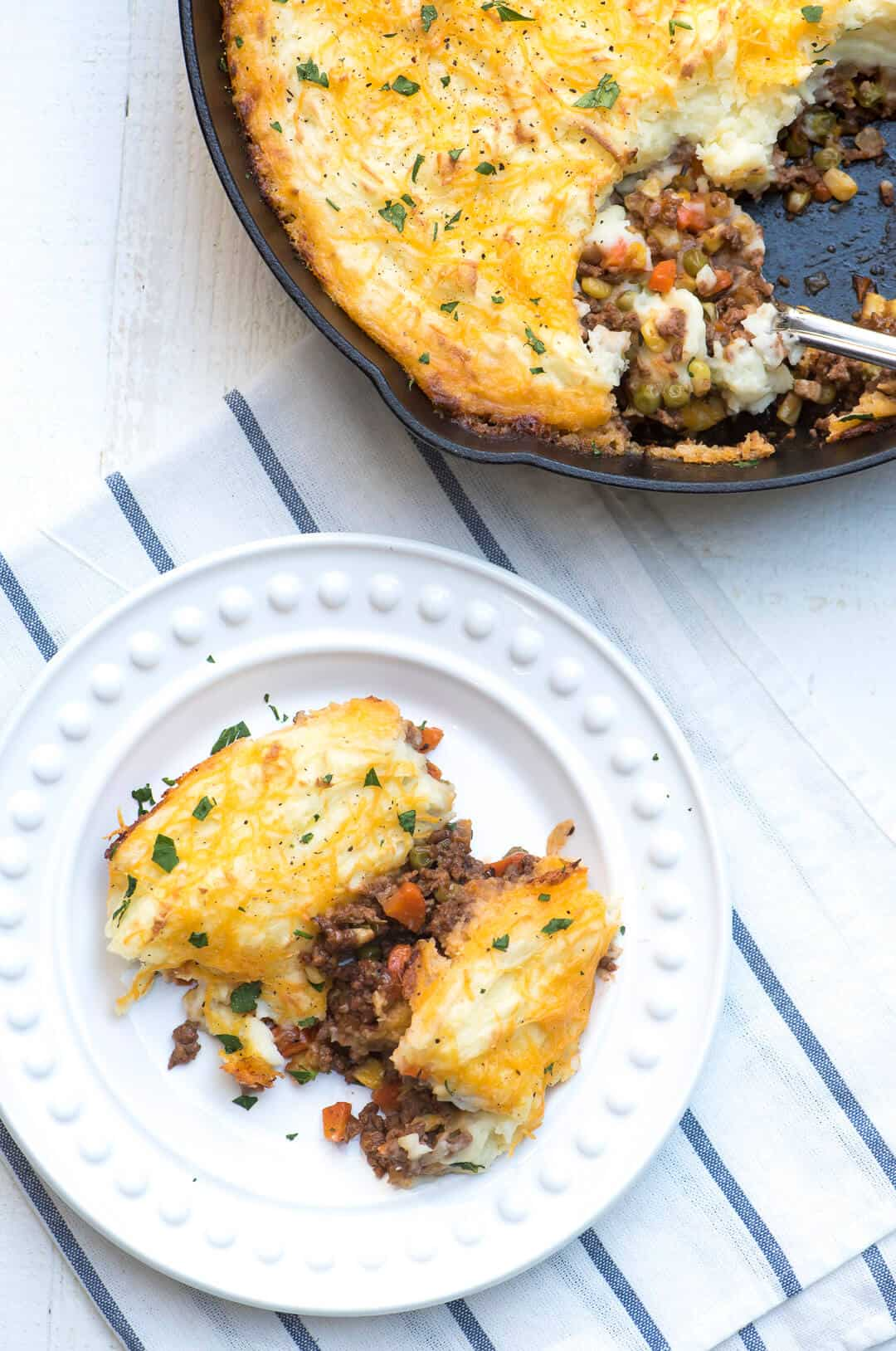 An over the top image of a serving of Skillet Shepherd's Pie on a white plate with the skillet in the background.