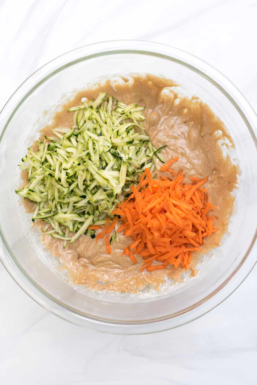 The batter in a clear glass mixing bowl with shredded carrot and zucchini on top.