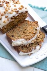 Slices of frosted Carrot Zucchini Bread on a white platter.
