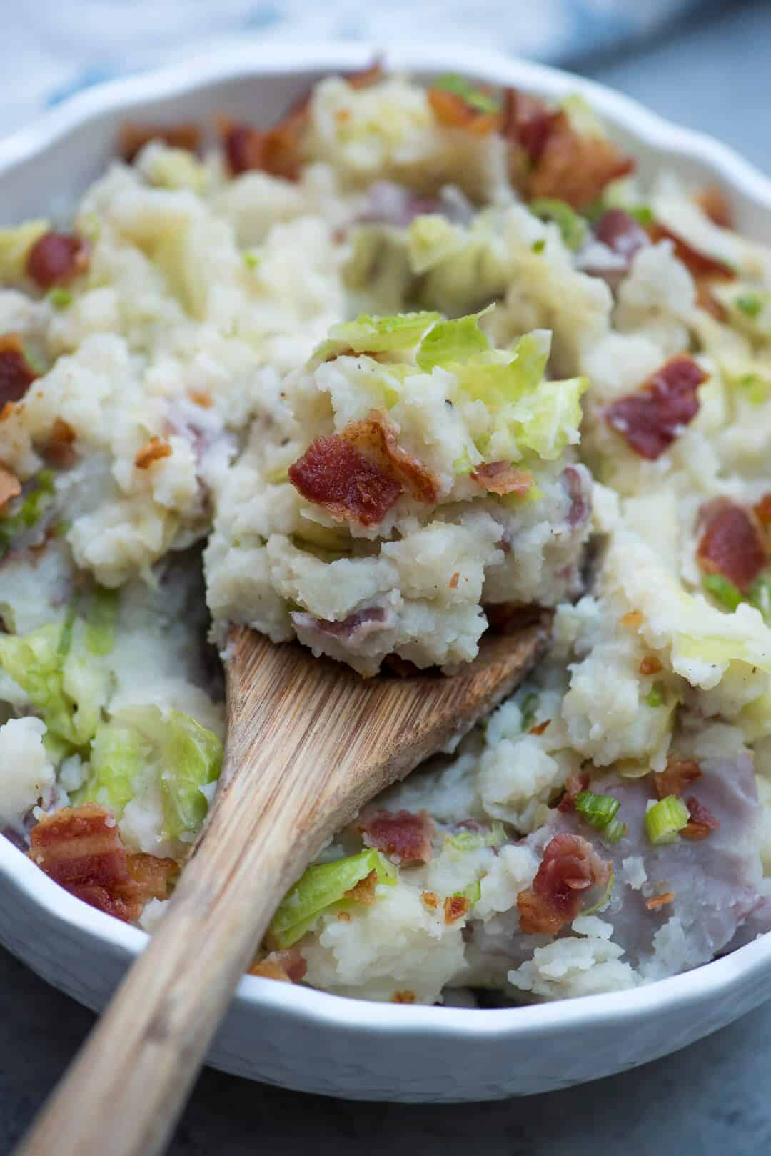 Irish Colcannon Potatoes in a white bowl with a wooden spoon.