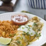 A smothered burrito topped with sour cream on a plate with rice.