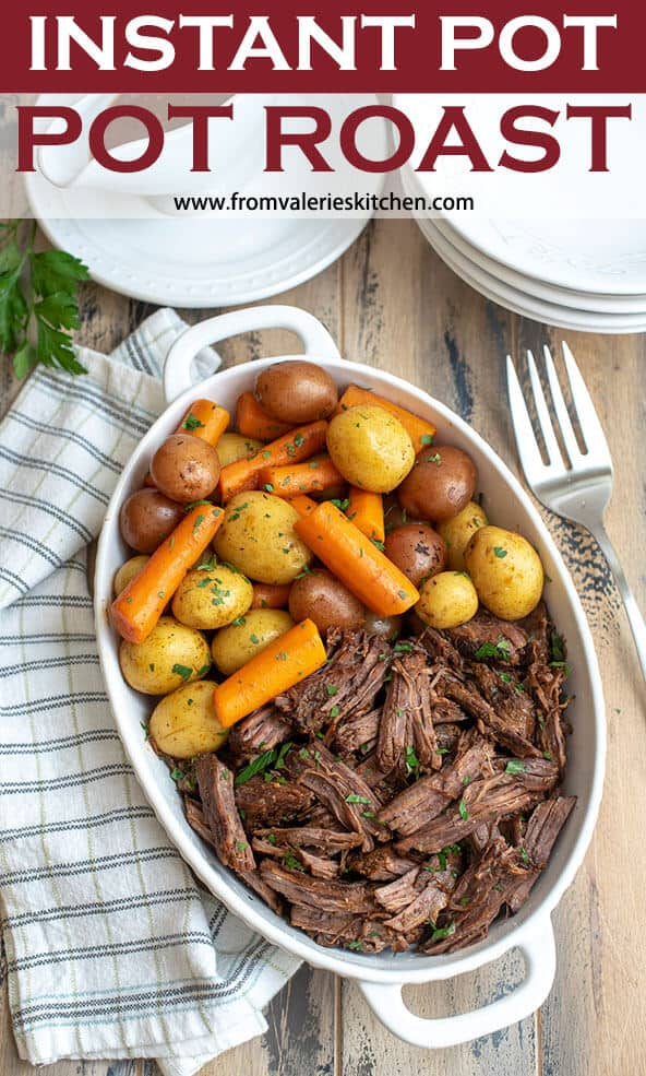 Pot roast with carrots and potatoes in a white serving dish with a kitchen towel and fork next to it with text overlay that reads Instant Pot Pot Roast