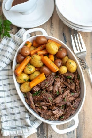A white serving dish filled with shredded beef, carrots, and potatoes.
