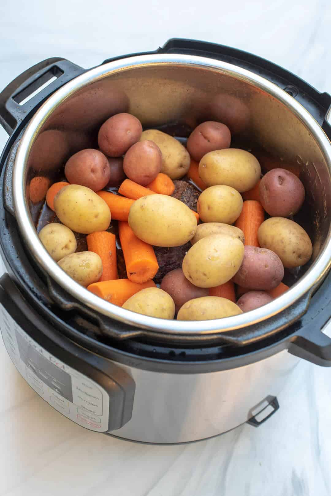 The beef roast, liquid, and vegetables in the Instant Pot.