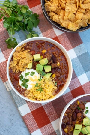 A bowl of chili topped with cheese, avocado, sour cream, and crushed corn chips.
