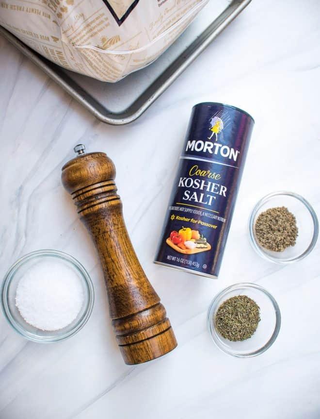 The dry brine ingredients - kosher salt, fresh ground black pepper, sage, and thyme.