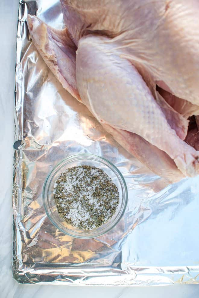 The dry brine ingredients combined in a small bowl next to the turkey.