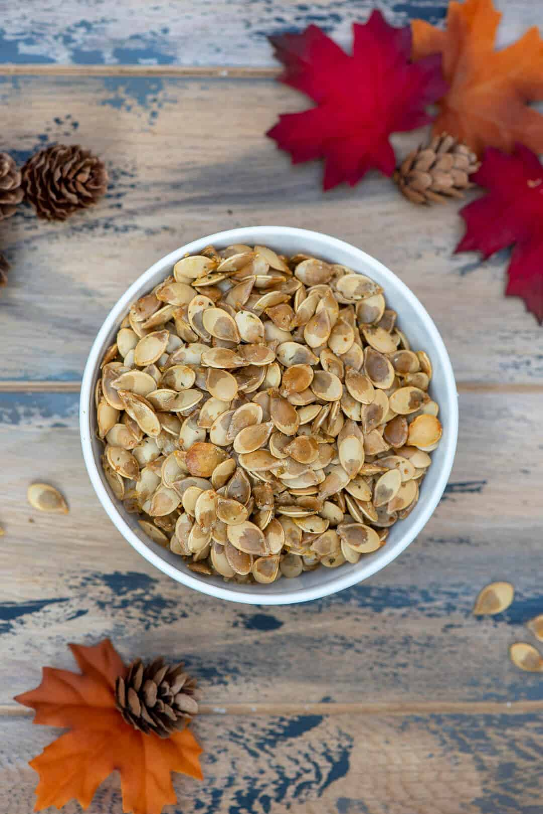 An over the top shot of the seeds in a white bowl with fall leaves and pine cones scattered around it.