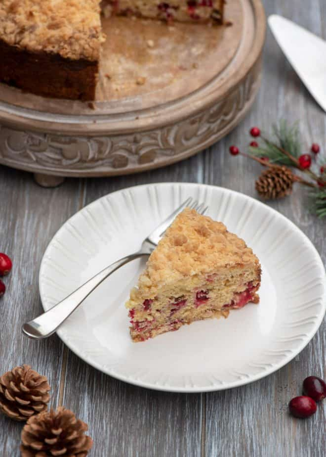 A slice of Cream Cheese Cranberry Coffee Cake on a white plate with a fork with pine cones scattered around.