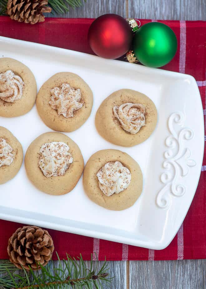 White thumbprint cookies filled with a creamy filling and dusted with nutmeg on a white platter.