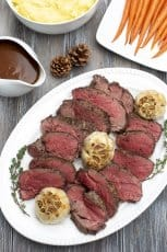 Slices of beef tenderloin with garlic on a white platter,