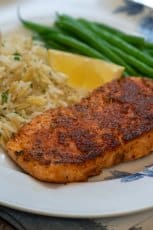 A piece of blackened salmon on a plate with rice and a slice of lemon.
