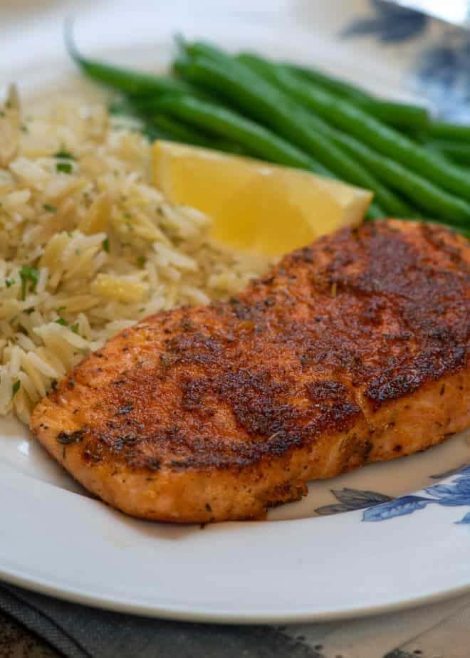A close up image of a piece of Blackened Salmon on a white plate with rice pilaf and green beans.