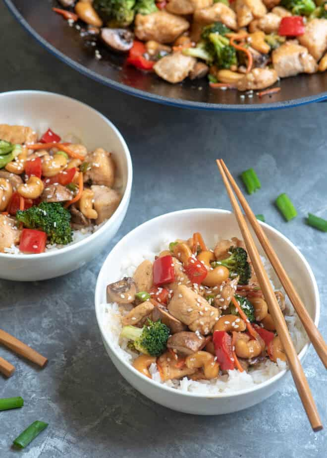 Two white serving bowls filled with Cashew Chicken with the wok in the backgroun.