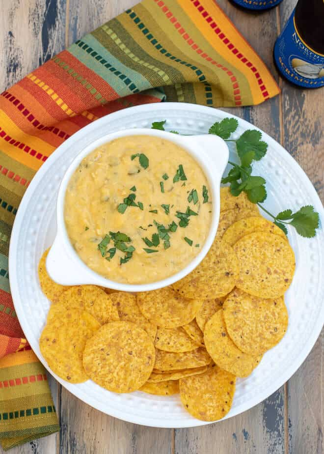 Slow Cooker Green Chile Chicken Queso on a serving platter with tortilla chips