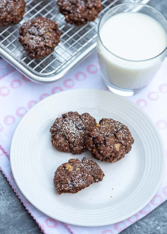 Chocolate Brownie Oatmeal Cookies on a small white plate with a glass of milk