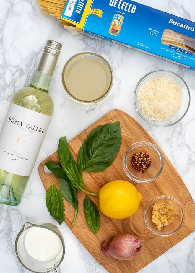 The ingredients to make Creamy Lemon Chicken with Pasta - bucatini pasta, dry white wine, chicken broth, Parmesan, cream, fresh basil, lemon, crushed red pepper flakes, garlic, and shallots
