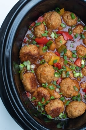 A slow cooker insert filled with chicken meatballs, sauce, and red bell peppers.