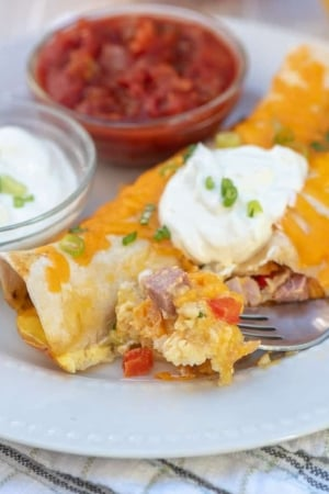 A breakfast enchilada with a fork on a white plate.