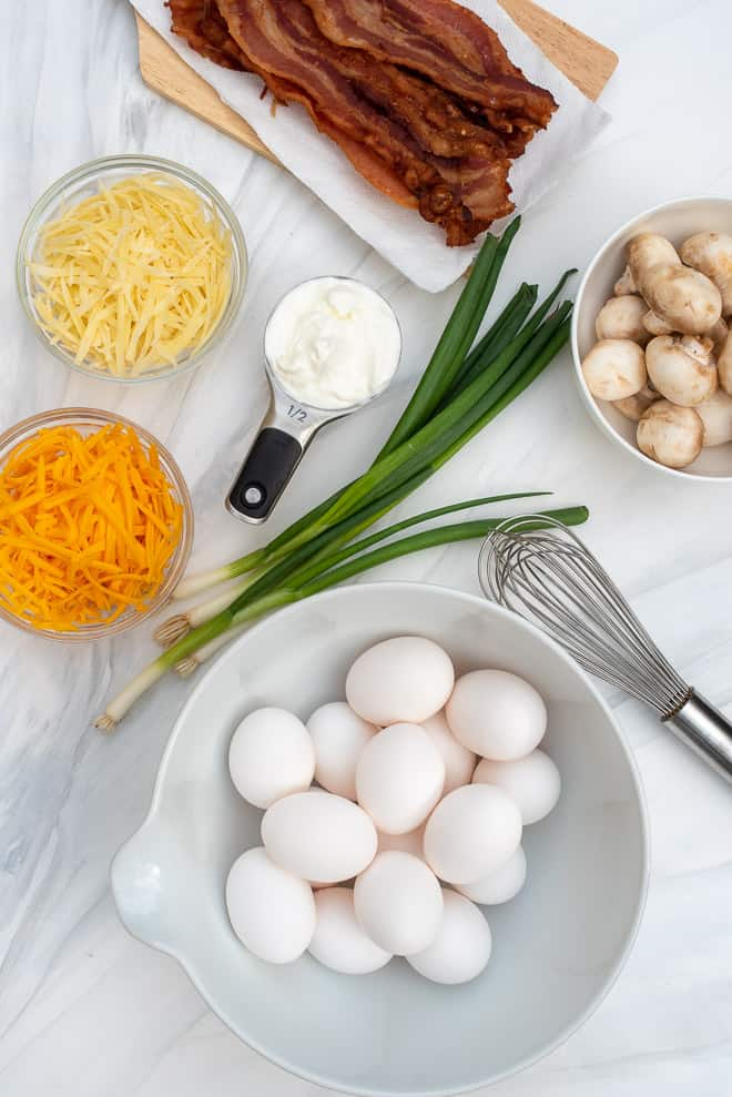 An over the top shot of the ingredients for Easy Crustless Quiche - eggs, shredded cheese, sour cream, green onions, bacon, and mushrooms.